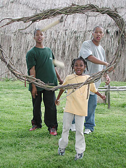 Kids try an Indian game at the Woodland Indian Hamlet.